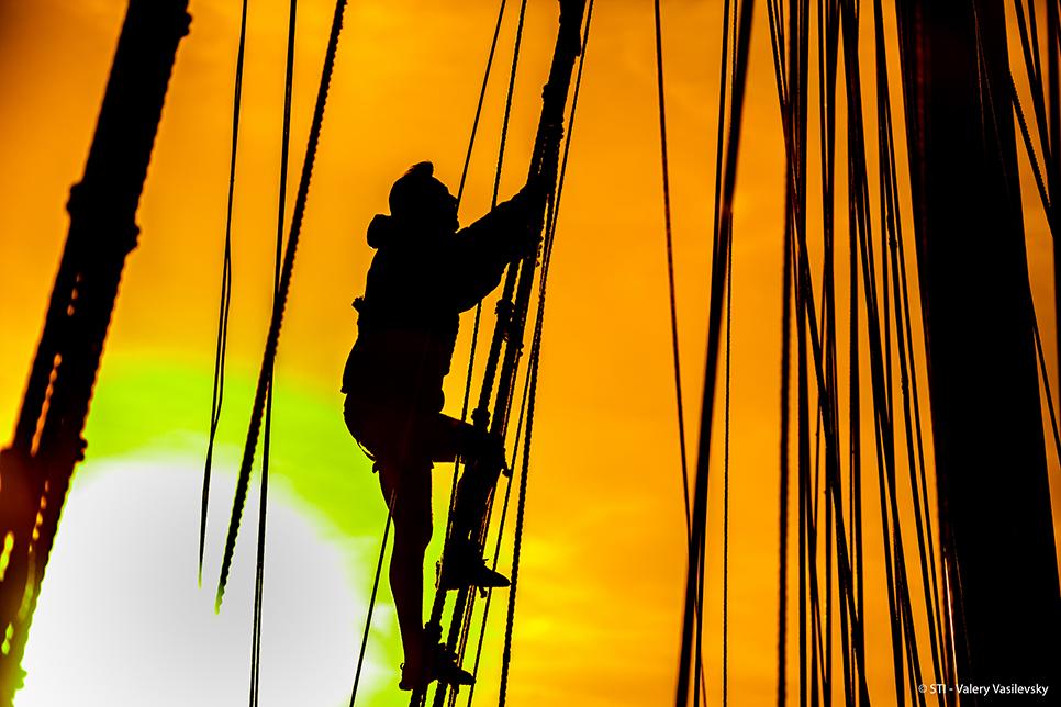 man climbing tall ship rigging