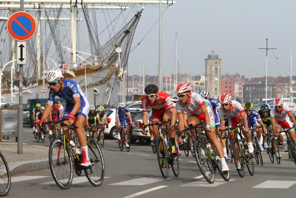 Cyclists racing past a tall ship during Four Days of Dunkirk race