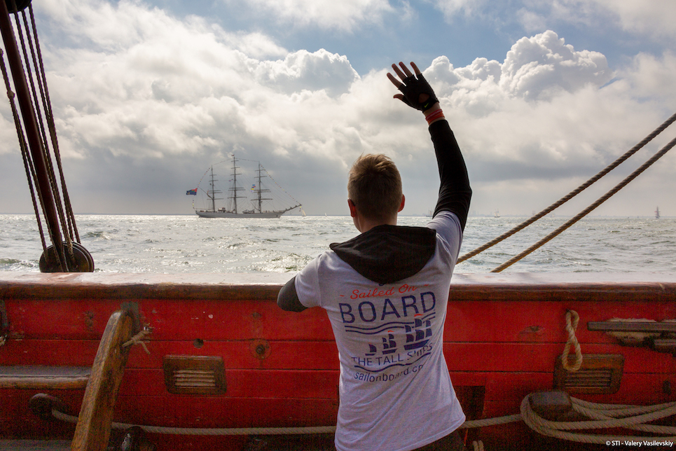 Shtandart crew member waving at tall ship sailing into The Hague for the liberty tall ships regatta 2019