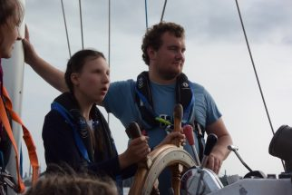 Two Crew Members Manning Helm with Adventure Under Sail